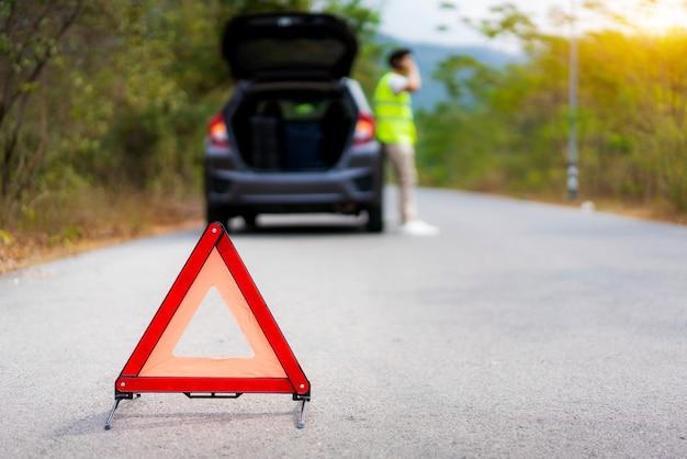 Aufschlüsselungsdreieckzeichen auf straße mit besorgtem asiatischem mann, der per handy mit versicherung oder autodienstleistungsunternehmen nach autounfall auf landstraße spricht