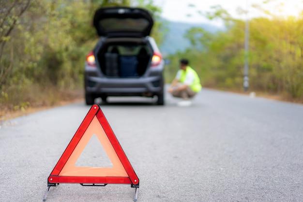 Aufschlüsselungsdreieckzeichen auf straße mit besorgtem asiatischen mann, der reifen repariert und wechselt, während er versicherung oder autoservice-zentrum wartet