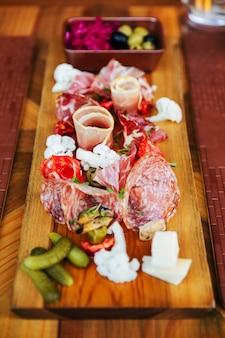 Aufschnitt auf holzbrett mit schinken, speck, salami und würstchen. fleischplatte vorspeisen serviert mit gurke und oliven am esstisch.