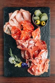 Aufschnitt auf steinplatte mit prosciutto, speck, salami und würsten.