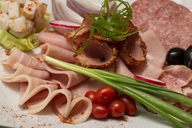 Aufschnitt auf verschiedenen plateausorten, speck, salami, tomaten, zwiebeln, grüne blätter, oliven