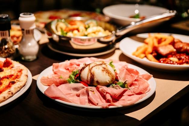 Aufschnitt burratina: burrata-käse, serviert mit parmaschinken, mortadella und salat.