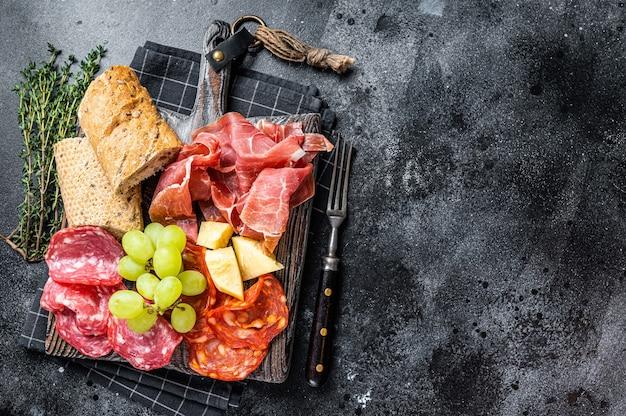 Aufschnittplatte, wurstwaren - traditionelle spanische tapas auf einem holzbrett mit brot und trauben. schwarzer tisch. draufsicht.