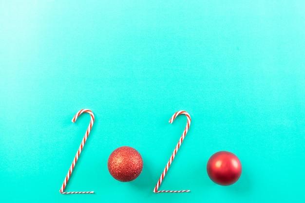 Aufschrift 2020 von der zuckerstange und vom roten ball, auf pastellgrünbuchhintergrund.
