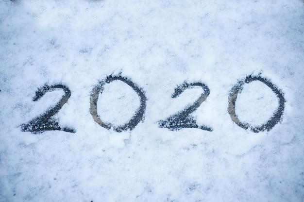 Aufschrift auf dem schnee 2020. weihnachtsfeiertagshintergrund