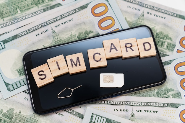 Aufschrift auf würfeln und sim-karte und auf dem smartphone und dollar-banknoten