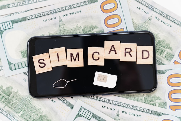 Aufschrift auf würfeln und sim-karte und auf smartphone und dollar-banknoten. konzept der zahlung für handy und internet. tägliche kommunikationskosten