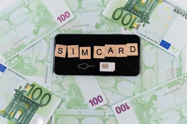 Aufschrift auf würfeln und sim-karte und auf smartphone und euro-banknoten.