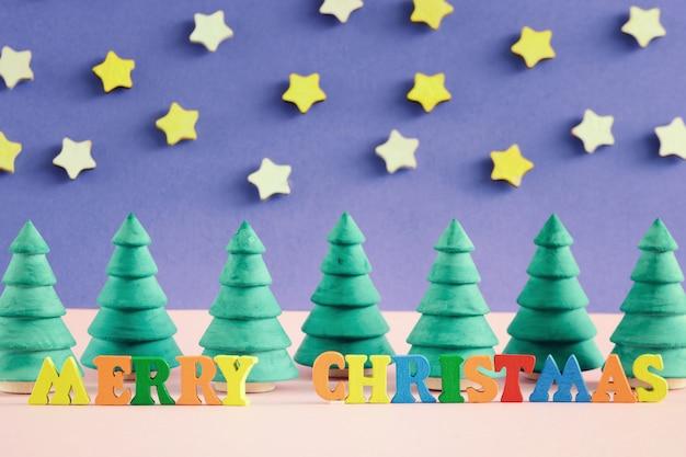 Aufschrift der frohen weihnachten in den bunten buchstaben.