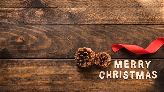 Aufschrift der frohen weihnachten nahe baumstümpfen und band