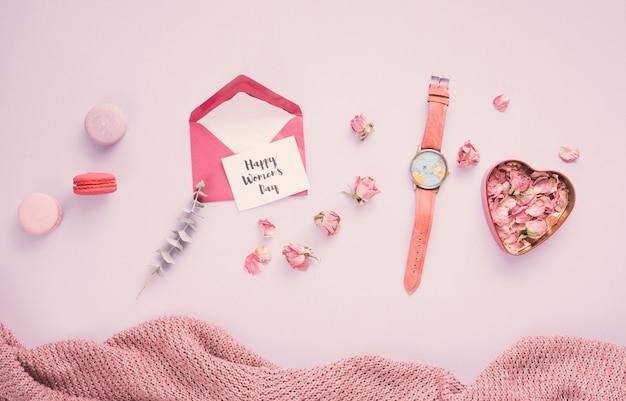 Aufschrift der glücklichen frauen tagesmit umschlag und den rosafarbenen blumenblättern
