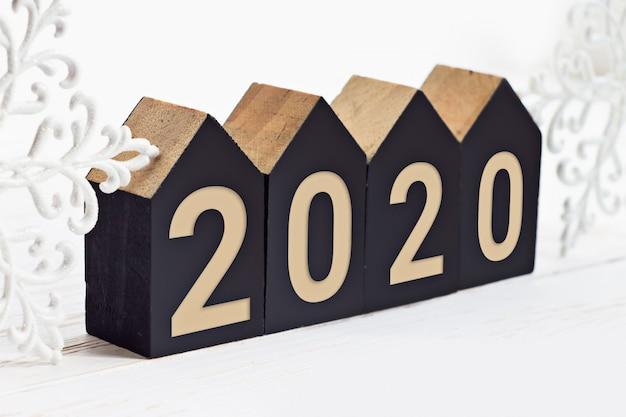 Aufschrift des neuen jahres 2020 auf hölzernen würfeln in form eines hauses auf einem weißen hölzernen hintergrund