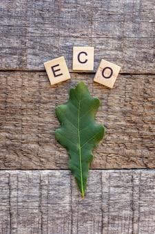 Aufschrift eco buchstaben wort und eichenblatt auf altem rustikalem holzhintergrund