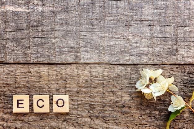 Aufschrift eco buchstaben wort und jasminblume auf altem rustikalem holzhintergrund