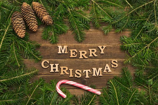 Aufschrift frohe weihnachten auf einer holzoberfläche mit kiefernbrances und -kegeln