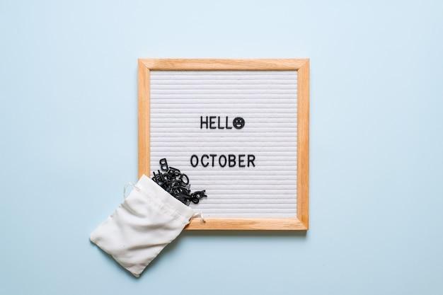Aufschrift hallo oktober auf weißem briefbrett, mit trockenen blättern auf hellblauem hintergrund. herbstkonzept