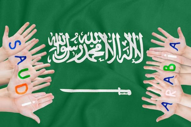 Aufschrift saudi-arabien auf den händen der kinder vor dem hintergrund einer wehenden flagge saudi-arabiens