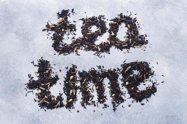Aufschrift-tee von trockenen teeblättern und -blumen auf einem grauen hintergrund.