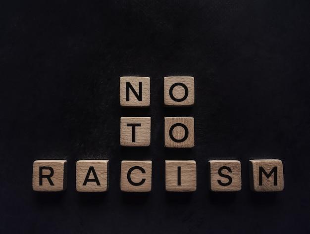Aufschrift von holzbuchstaben nein zu rassismus auf schwarzem hintergrund.