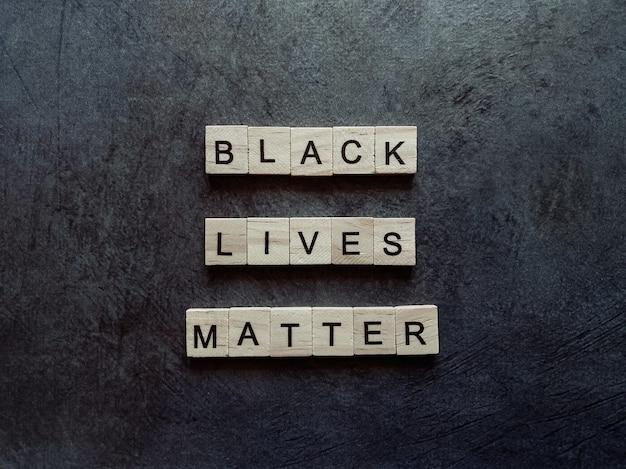 Aufschrift von holzbuchstaben schwarze leben ist auf dunklem hintergrund wichtig.