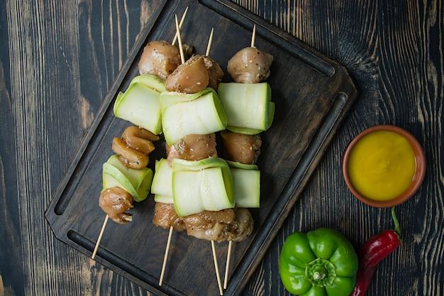 Aufsteckspindeln auf einem spieß mit zucchini mit soße, gemüse und kräutern auf einem schneidebrett. dunkles holz.