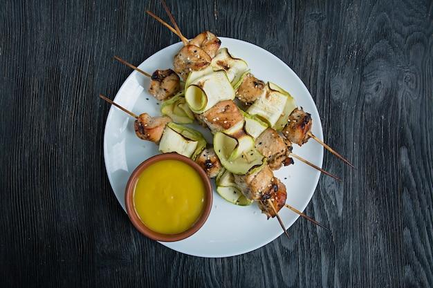 Aufsteckspindeln auf einer aufsteckspindel mit zucchini mit soße, gemüse und kräutern auf einer weißen platte. dunkles holz.