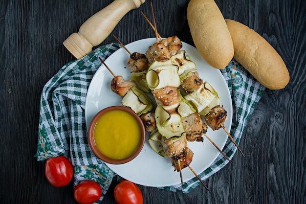 Aufsteckspindeln auf einer aufsteckspindel mit zucchini mit soße, gemüse und kräutern auf einer weißen platte.