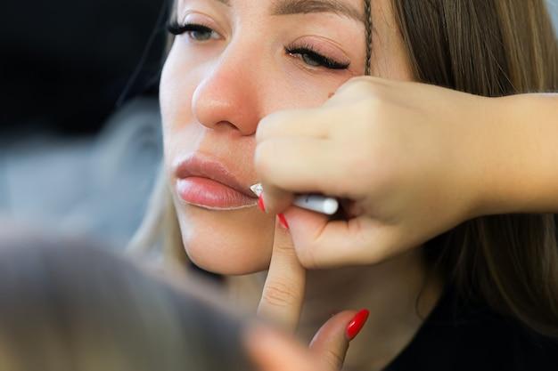 Auftragen der kontur auf die lippen mit einem weißen stift vor dem permanenten lippen-make-up