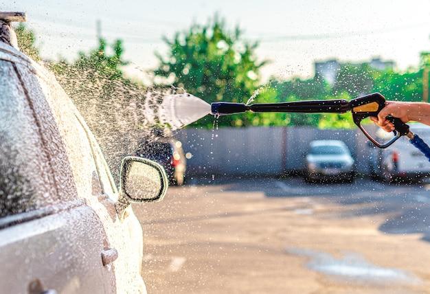 Auftragen von waschschaum auf das auto an der autowaschstation