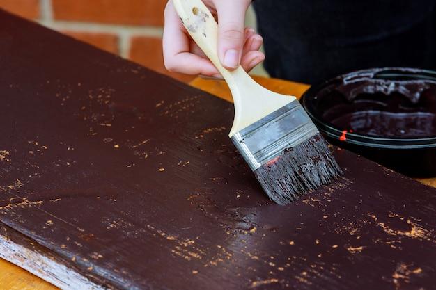 Auftragnehmer, der eine hölzerne fußleiste für die renovierung malt