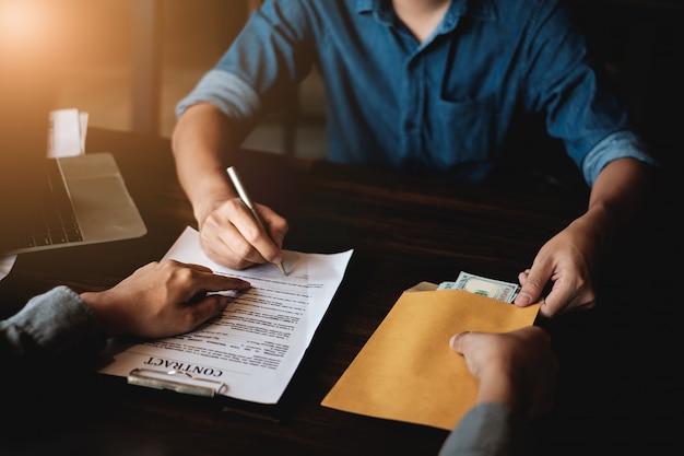 Auftragnehmer geben einem anderen geschäftsmann bestechungsgeld im umschlag und zeigen auf zeichenerlaubnisvertrag.