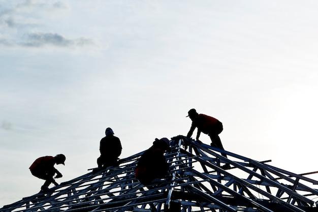 Auftragnehmer im schattenbild, das an eine dach-oberseite arbeitet