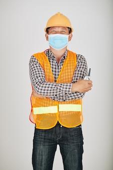 Auftragnehmer in sicherheitsweste und medizinischer maske