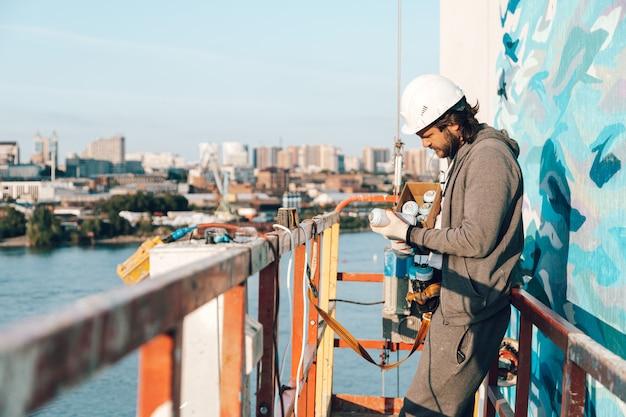 Auftragnehmer, künstler in großer höhe in einer gebäudewiege führt fassadenmalerei, dekoration und renovierung durch