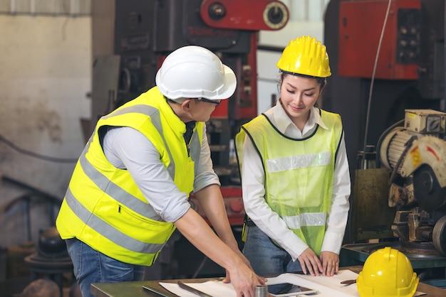 Auftragnehmer und ingenieur mit bauplänen diskutieren in einer modernen fabrik