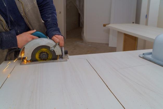 Auftragnehmer verwendet eine säge, um durch eine arbeitsplatte aus laminat-küchenformica zu schneiden