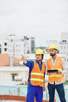 Auftragnehmer zeigt fertige arbeiten dem stirnrunzelnden chefingenieur des projekts mit digitalem tablet in händen