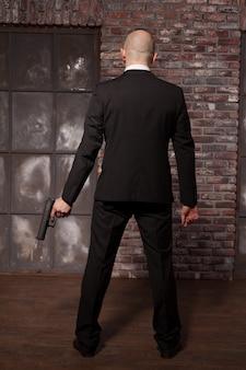Auftragsmörder mit waffentapetenkonzept, rückansicht. der kahle attentäter im anzug hält die waffe in der hand. geheimagent auf mission