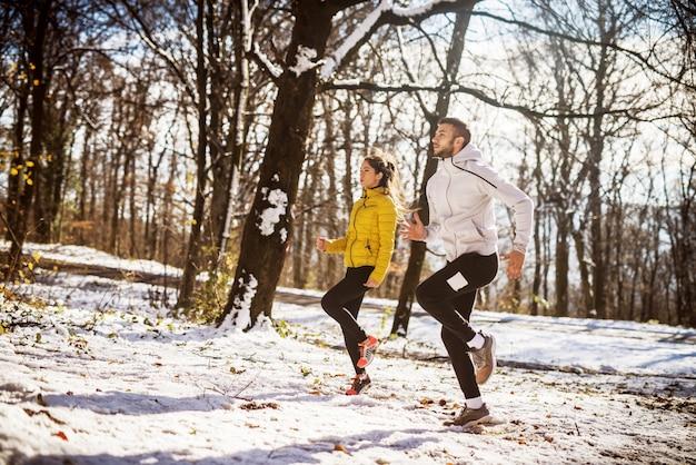 Aufwärmen des paares vor dem laufen in der natur. winter und kaltes wetter.