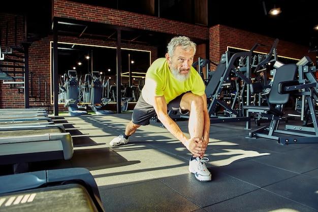 Aufwärmen des porträts eines athletischen mannes mittleren alters in sportbekleidung, der die beine vor dem training in einem streckt