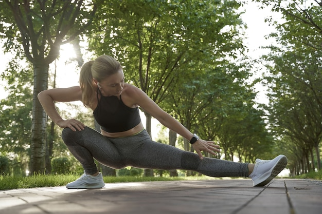 Aufwärmen im freien in voller länge der schönen fitnessfrau in sportkleidung, die ihre beine streckt, während