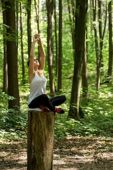 Aufwärmen. schönes sportliches mädchen im wald auf einem baumstumpf im yoga, sport