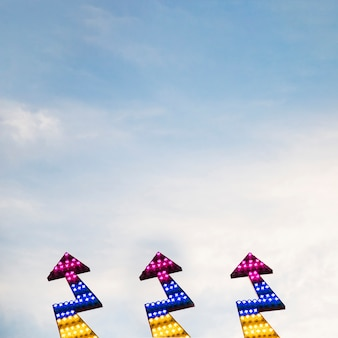Aufwärts gerichtete ikone des blitzpfeiles gegen himmel