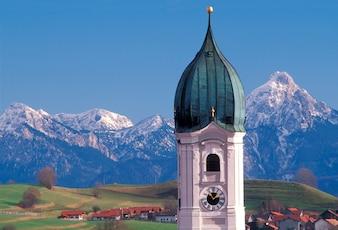 Aufwändige Haube des Glockenturms über wunderlichem Ferndorf mit schneebedeckten Bergen im Hintergrund