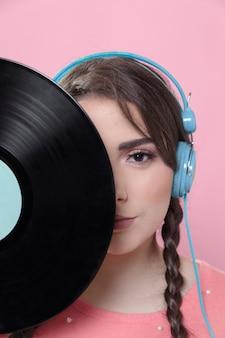 Aufwerfende frau beim bedecken der hälfte des gesichtes mit vinylaufzeichnung