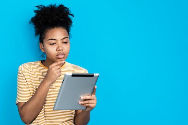 Aufwerfende frau beim denken und halten der tablette