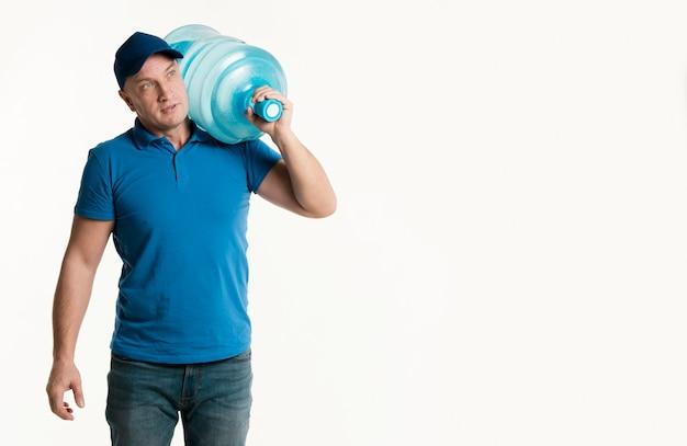 Aufwerfender lieferer beim tragen der wasserflasche