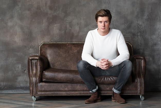 Aufwerfender mann beim sitzen auf couch mit kopienraum