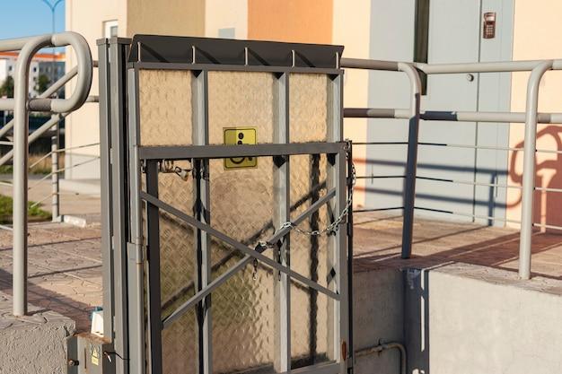 Aufzug für menschen mit behinderungen am eingang eines mehrfamilienhauses. unterstützung für personen, die sich im rollstuhl bewegen.
