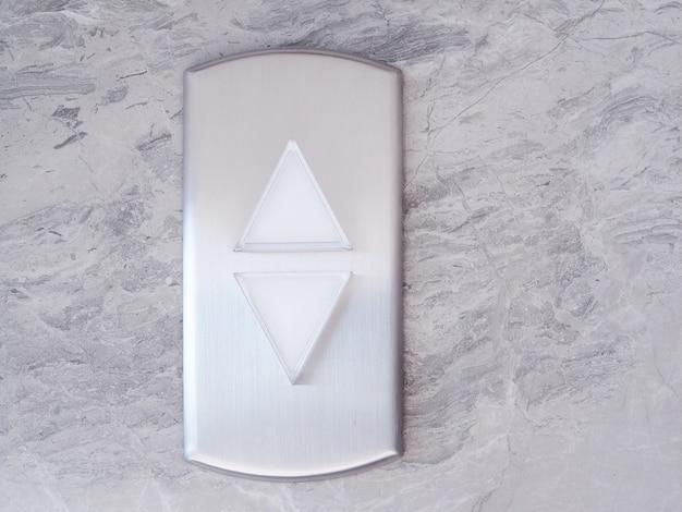 Aufzug mit silbernem knopfdreieck auf und ab auf marmormusterwand.